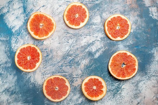 Bovenaanzicht cirkel rij gesneden grapefruits blauw witte tafel