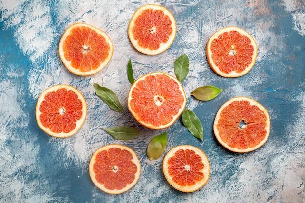 Bovenaanzicht cirkel rij gesneden grapefruits verlaat blauwe witte tafel