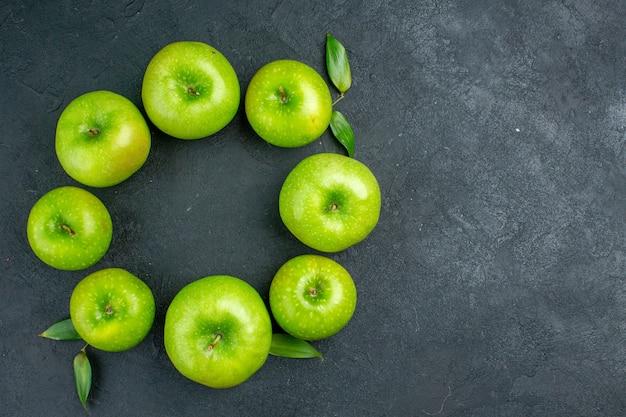 Bovenaanzicht cirkel rij groene appels op donkere tafel kopie ruimte