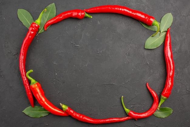 Bovenaanzicht cirkel van rode hete pepers en bladeren op zwarte ondergrond