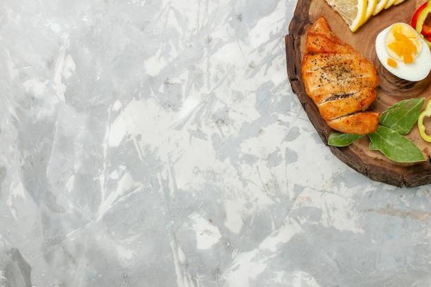 Bovenaanzicht citroen en groenten met broodje op lichte witte bureau groenten eten maaltijd lunch