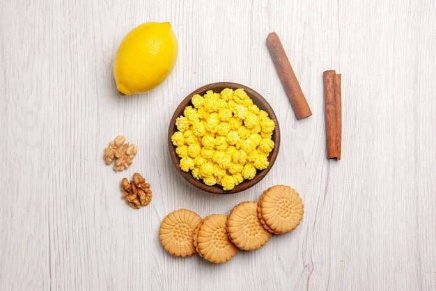 Bovenaanzicht citroen en snoep, kaneelstokjes, koekjes, noten, kom met gele snoepjes en citroen op de witte tafel