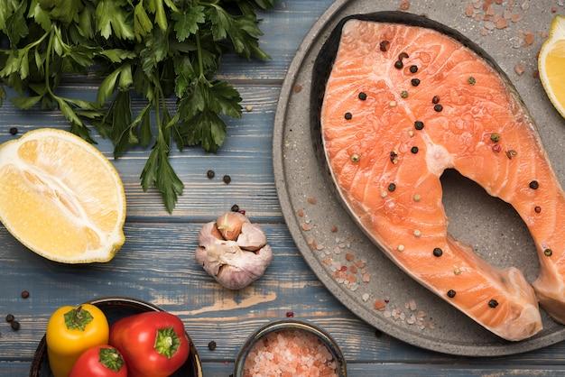 Bovenaanzicht citroen en zalm steak op dienblad met ingrediënten
