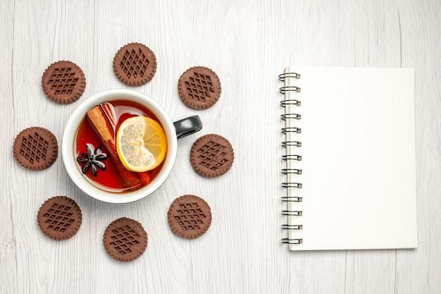 Bovenaanzicht citroen-kaneelthee afgerond met koekjes en een notitieboekje op de witte houten tafel