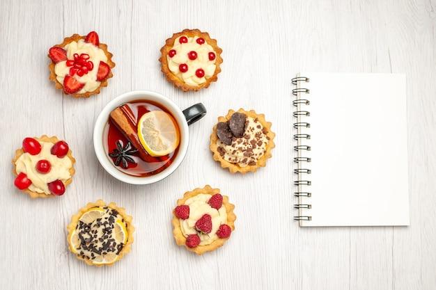 Bovenaanzicht citroen-kaneelthee afgerond met taartjes en een notitieboekje op de witte houten tafel
