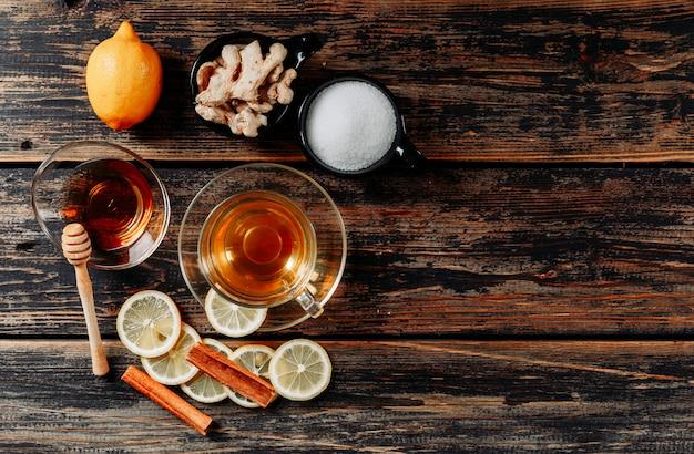 Bovenaanzicht citroen met gember, honing, droge kaneel, thee op donkere houten achtergrond. ruimte voor tekst