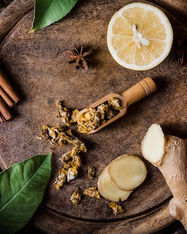 Bovenaanzicht citroen met kruiden en gember op snijplank