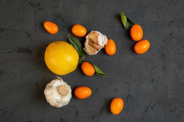 Bovenaanzicht citroen met kumquat en knoflook op zwart