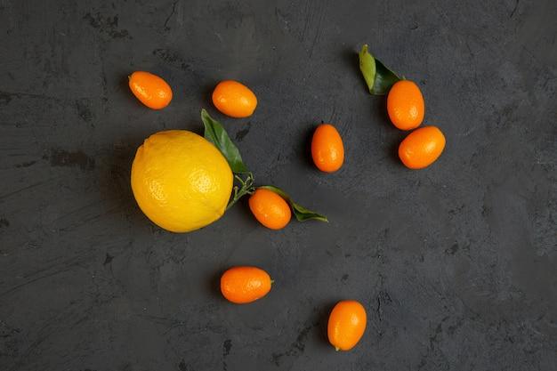 Bovenaanzicht citroen met kumquat op zwart