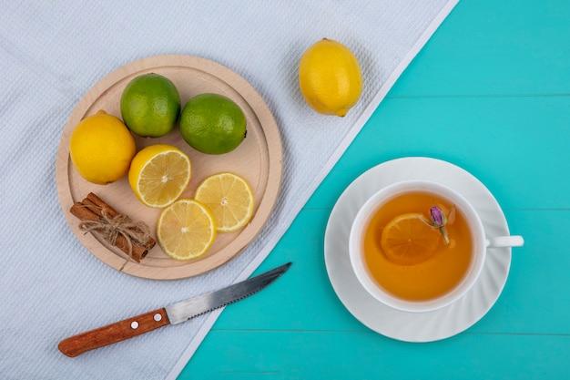 Bovenaanzicht citroen met limoen op een dienblad met kaneel een mes en een kopje thee op een witte handdoek op een lichtblauwe achtergrond