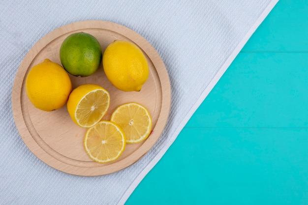 Bovenaanzicht citroen met limoen op een dienblad op een witte handdoek op een lichtblauwe achtergrond