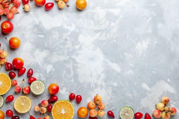 Bovenaanzicht citroenen en kersen vers fruit op het licht bureau fruit vers zacht rijp