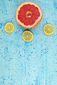 Bovenaanzicht citroenen grapefruits gesneden mellow rijp op de heldere blauwe achtergrond