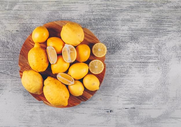 Bovenaanzicht citroenen in houten platform met plakjes op grijze houten achtergrond. horizontale ruimte voor tekst