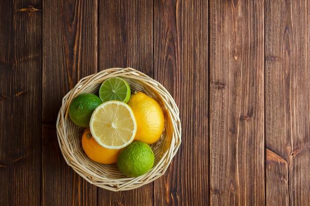 Bovenaanzicht citroenen in mand op houten achtergrond.