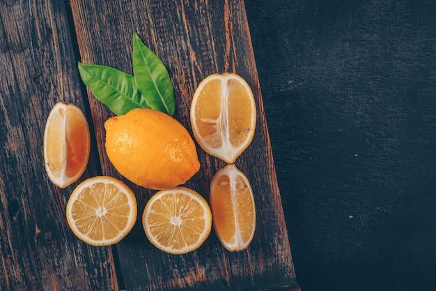 Bovenaanzicht citroenen met bladeren en segmenten op houten dienblad en zwarte gestructureerde achtergrond. horizontaal