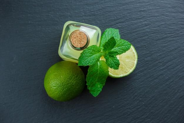Bovenaanzicht citroenen met citroensap en bladeren op donkere stenen ondergrond. verticaal