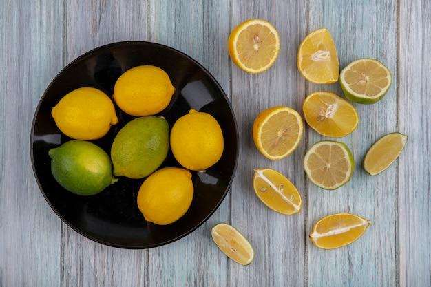Bovenaanzicht citroenen met limoen op een zwarte plaat met wiggen op een grijze achtergrond
