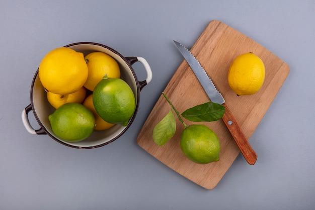 Bovenaanzicht citroenen met limoenen in een pan met een mes op een snijplank op een grijze achtergrond