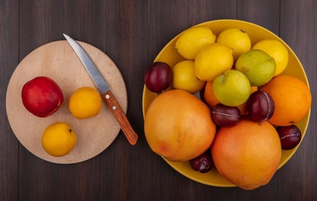 Bovenaanzicht citroenen met sinaasappels, pruimen en grapefruit in een gele kom met abrikozen en een perzik op een stand met een mes op een houten achtergrond