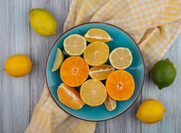 Bovenaanzicht citroenpartjes met limoen en sinaasappel op een bord op een gele geruite handdoek op een grijze achtergrond