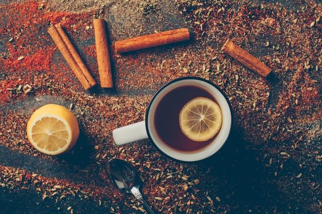 Bovenaanzicht citroenthee en gedroogde kruiden met droge kaneel, lepel en citroen