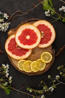 Bovenaanzicht citrus stukken ringen zachte rijpe zure grapefruits en citroenen op het bruine bureau en donker