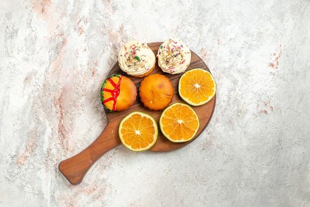 Bovenaanzicht citrusvruchten gesneden citrusvruchten en koekjes op de snijplank op het lichte oppervlak