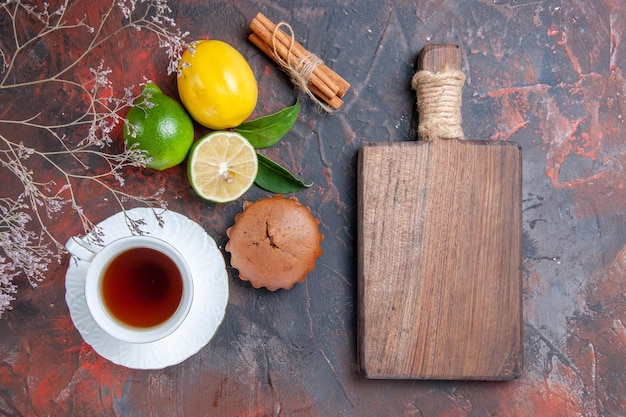 Bovenaanzicht citrusvruchten kaneel een kopje thee citroen limoen cupcake boomtakken de snijplank
