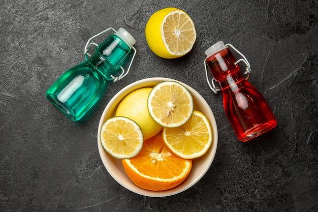 Bovenaanzicht citrusvruchten kom met citrusvruchten naast de kleurrijke flessen op de donkere tafel