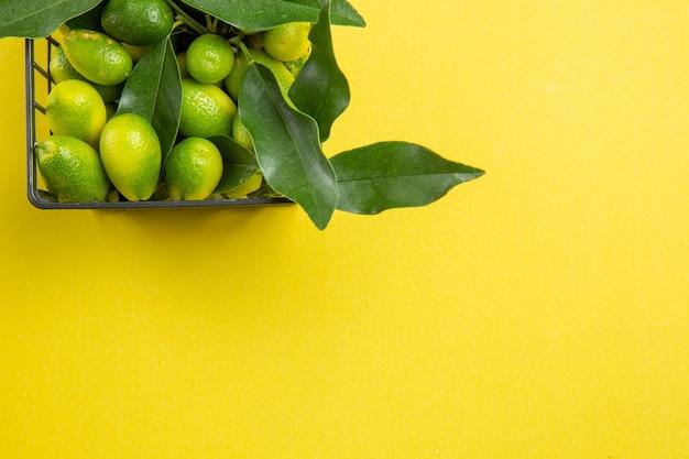 Bovenaanzicht citrusvruchten mand met groene citrusvruchten met bladeren