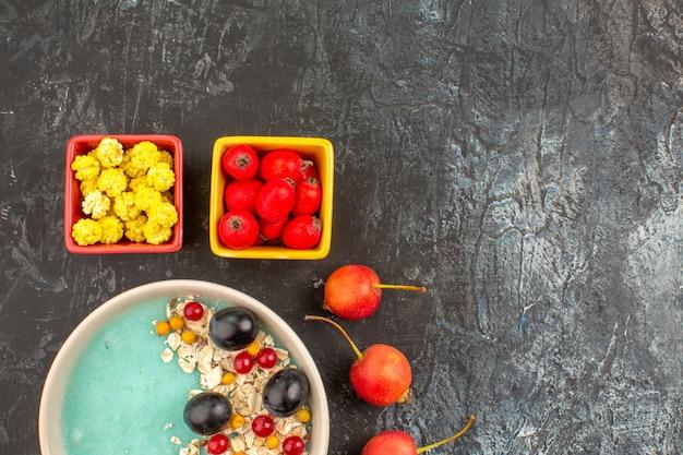 Bovenaanzicht close-up bessen gele snoepjes kersen kleurrijke bessen in de kommen