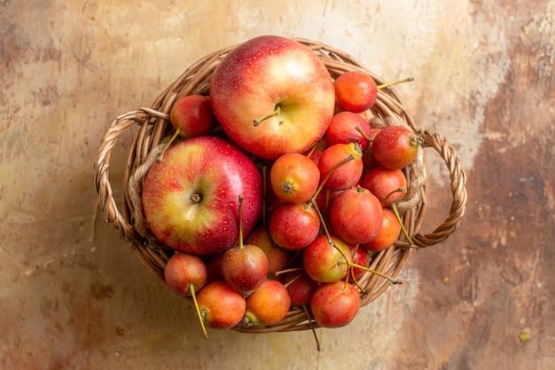 Bovenaanzicht close-up bessen houten mandje met appels bessen op tafel