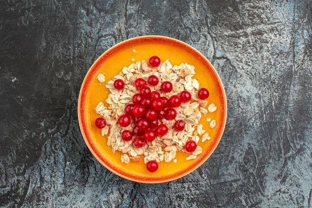 Bovenaanzicht close-up bessen rode aalbessen op de oranje plaat op de grijze tafel