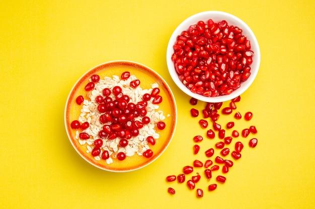Bovenaanzicht close-up bessen twee kommen bessen havermout en granaatappel zaden