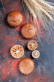 Bovenaanzicht close-up cupcakes drie cupcakes citroenen en tarwe oren op tafel
