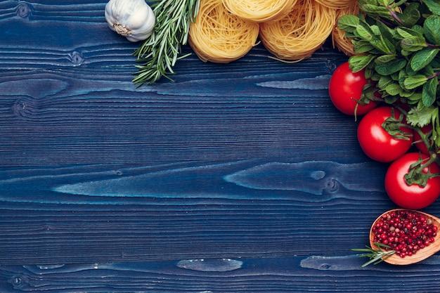 Bovenaanzicht close-up detail van tagliatelle italiaanse pasta op houten blauwe achtergrond