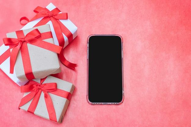 Bovenaanzicht close-up drie geschenkdozen. rood lint boog met geschenkdozen met smartphone op rode achtergrond, verpakte vintage doos met kopie ruimte