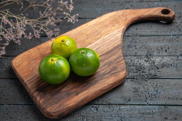 Bovenaanzicht close-up drie limoenen drie limoenen op keukenbord op tafel