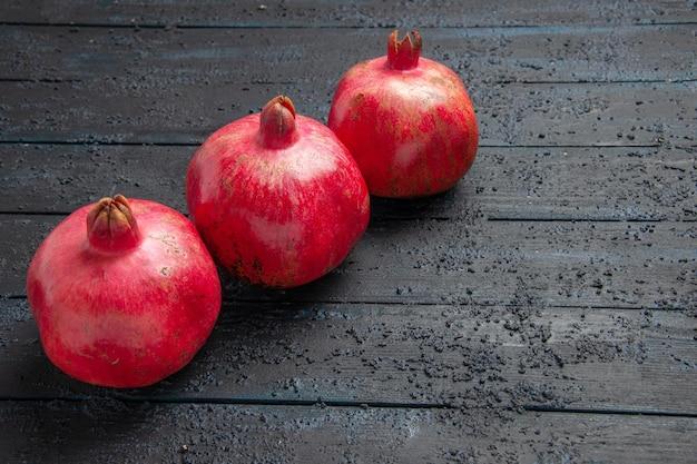 Bovenaanzicht close-up drie rijpe granaatappels granaatappels aan de liftzijde van houten grijze tafel