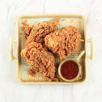Bovenaanzicht close-up gouden knapperige gebakken kipfilet en kippenvleugels, geserveerd op een rustieke vierkante plaat met chilisaus, geïsoleerd op een witte achtergrond met kopie ruimte voor tekst
