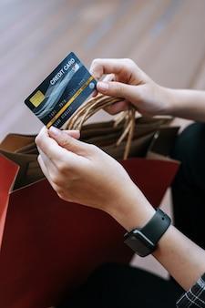 Bovenaanzicht, close-up hand van jonge vrouw met creditcard in de hand met boodschappentas