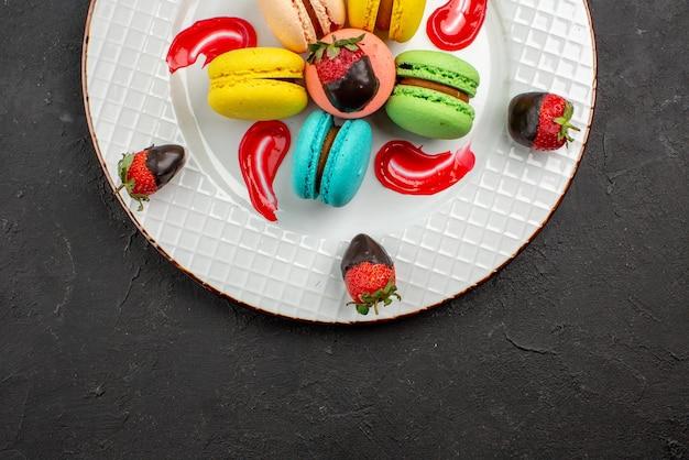 Bovenaanzicht close-up macaron met chocolade bedekte aardbeien bitterkoekjes en saus op de donkere tafel