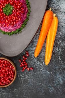 Bovenaanzicht close-up schotel granaatappel zaden lepel wortelen