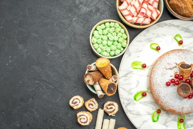 Bovenaanzicht close-up snoep een cake met rode aalbessen kleurrijke snoepjes wafels snoepjes