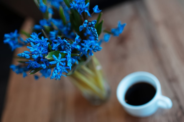Bovenaanzicht close-up van blauwe viooltjes bloemen op achtergrond van wazig houten tafel in de buurt van kopje koffie.
