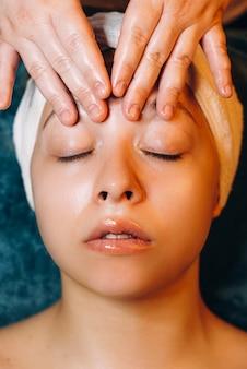 Bovenaanzicht close up van een charmante vrouw gezicht massage therapie in een wellness-centrum.