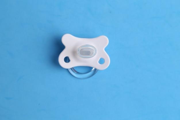 Bovenaanzicht close-up van een fopspeen van een baby die gebruikt werd om op te zuigen op een blauwe ondergrond