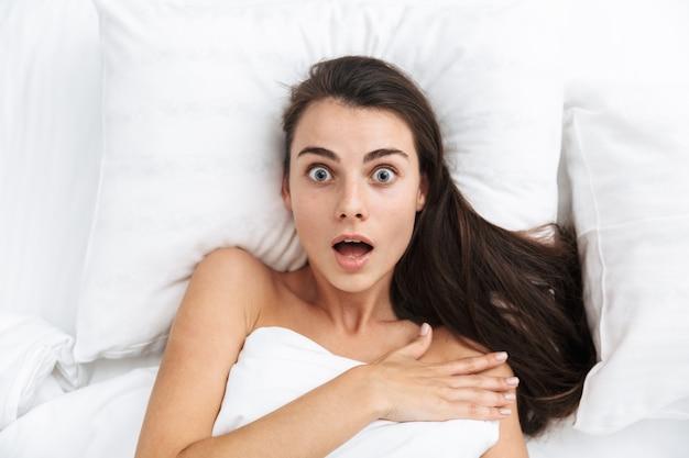 Bovenaanzicht close up van een mooie geschokt jonge vrouw tot in bed