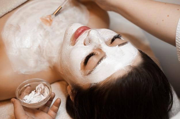 Bovenaanzicht close up van een mooie vrouw met donker haar met een wit masker op haar gezicht in een wellness-spa salon.